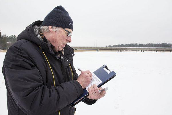 Kalastuksenvalvoja kirjoittaa kalastajalle huomastusta.